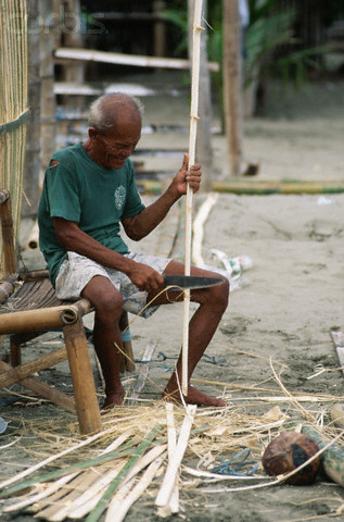 Man Whittling Bamboo in Village Near Iloilo, Panay